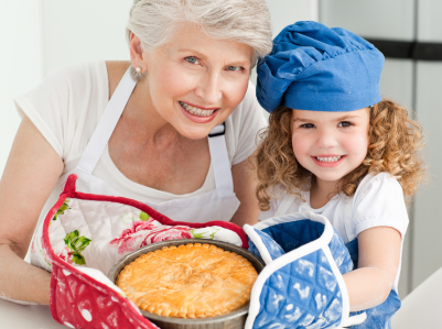 a grandma holding a baked pie with her grandchild